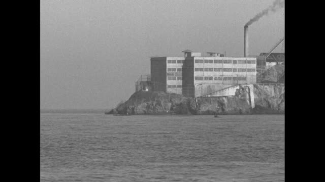 ws infamous prison facility alcatraz island surrounded by water / drive by part of the facility / tiltup shot guard walks on catwalk on prison... - prison escape stock videos and b-roll footage