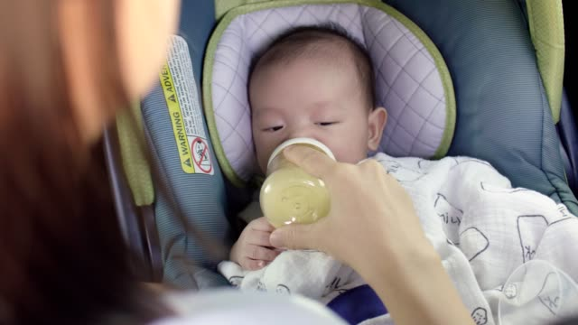 infant baby boy buckled into his car seat and drinking milk - seat stock videos & royalty-free footage