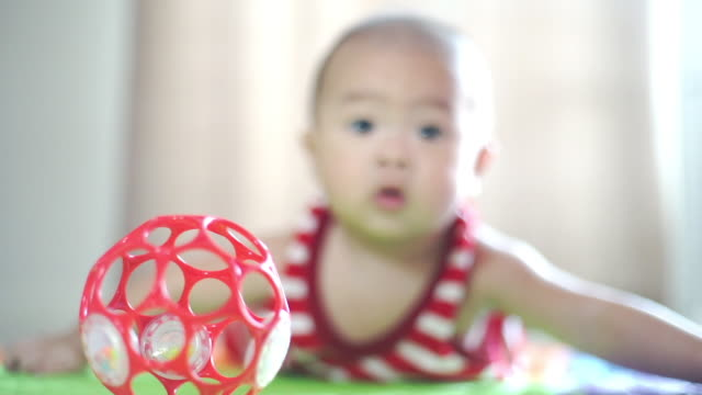 Infant baby boy crawling on the floor and looking at a ball.