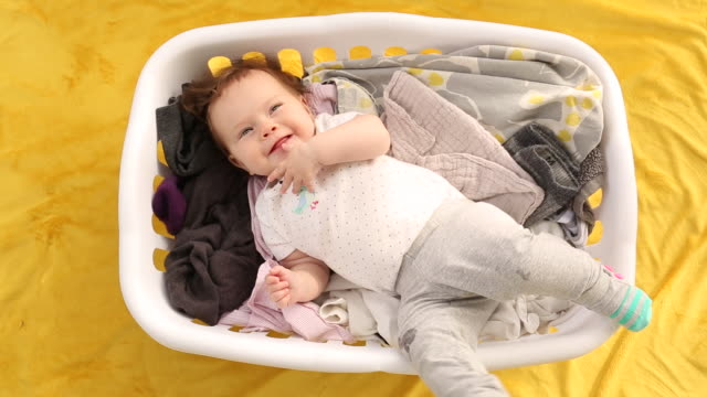a infant baby lying in a laundry basket filled with clothes. - lying on back stock videos & royalty-free footage