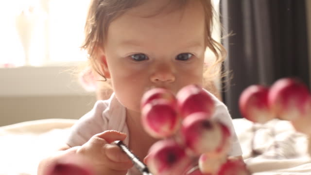 a infant baby playing with a decoration inside of her house. - strampelanzug stock-videos und b-roll-filmmaterial