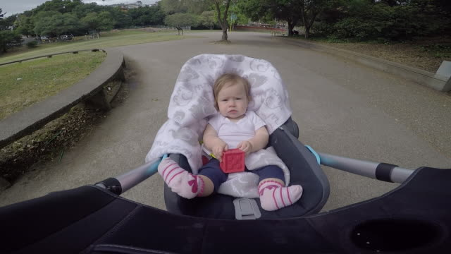 a infant baby riding in a stroller outdoors in a residential area. - walking point of view stock videos & royalty-free footage