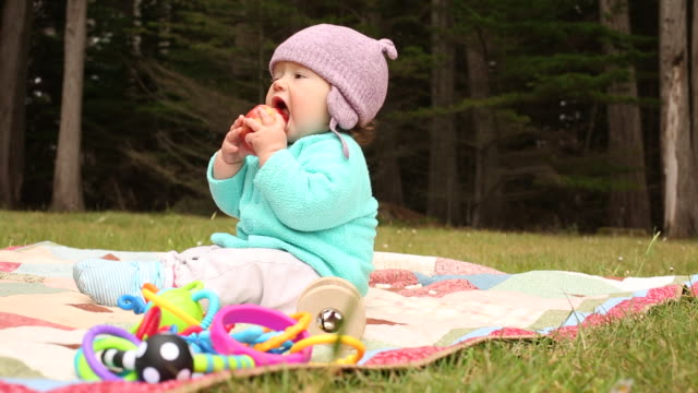 a infant baby sitting outside on a blanket and having fun with toys and food. - peach stock videos & royalty-free footage