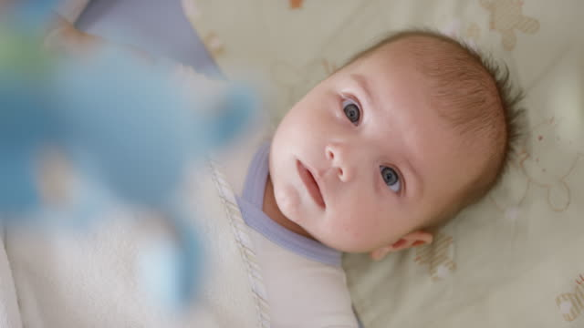 Infant boy observing baby mobile while lying in bed