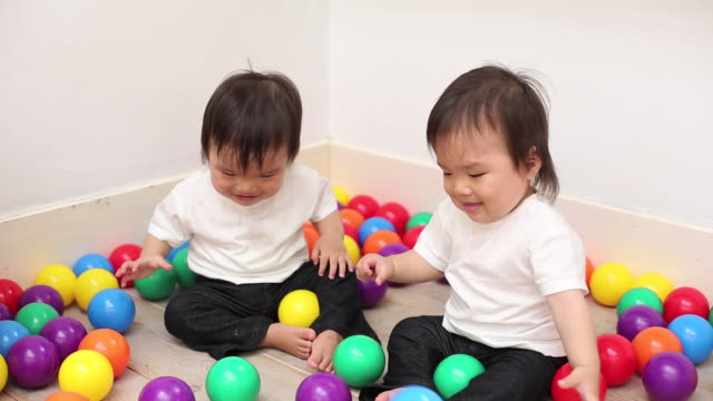 infant boy twins plays with colorful balls sitting on the floor at home - babies only stock videos & royalty-free footage