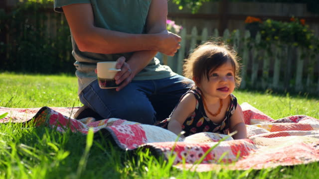 vídeos y material grabado en eventos de stock de ms infant girl playing with toy while sitting with father on blanket in backyard on summer morning - manta ropa de cama