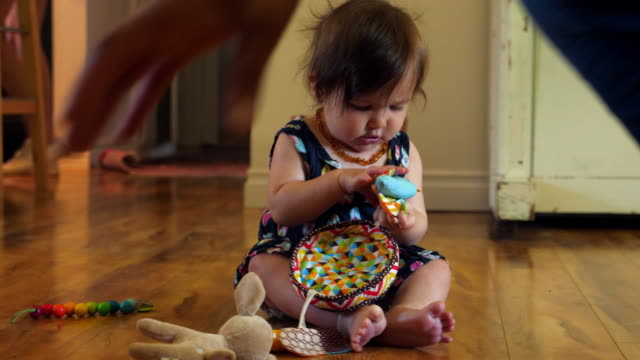 cu infant girl playing with toys while sitting on floor in living room - baby girls stock videos & royalty-free footage