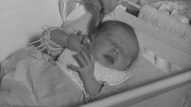 1940 montage infant in bassinet getting its hair combed with pediatric nurse and young mother overhead, kindergarten student eating lunch, and teacher giving prepared lunch to line of hungry preschoolers / united kingdom - 1940 stock videos and b-roll footage