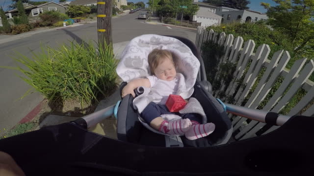 A infant sleeping inside of a stroller while walking in a residential area.
