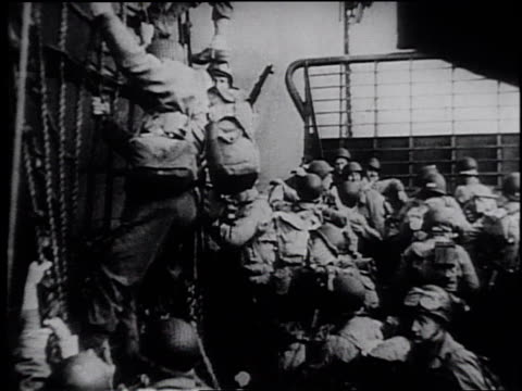 infantry advancing across a large field / soldiers climbing down a net on the side of a ship into a landing craft / shelling ashore in advance of a... - frank capra video stock e b–roll