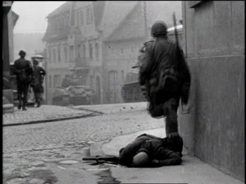 infantry advancing through city / soldiers following tank down the street / soldiers running through courtyard / soldiers stepping over dead enemy... - 1945 stock-videos und b-roll-filmmaterial