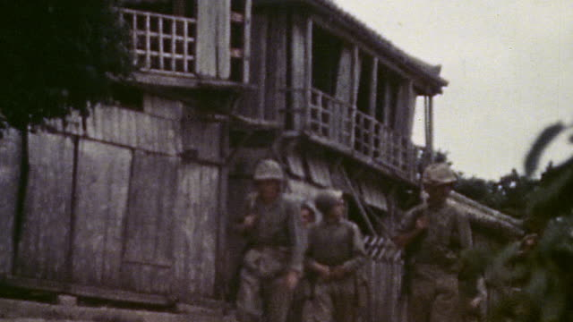 s infantry advancing through village during wwii / okinawa japan  - infanterie stock-videos und b-roll-filmmaterial