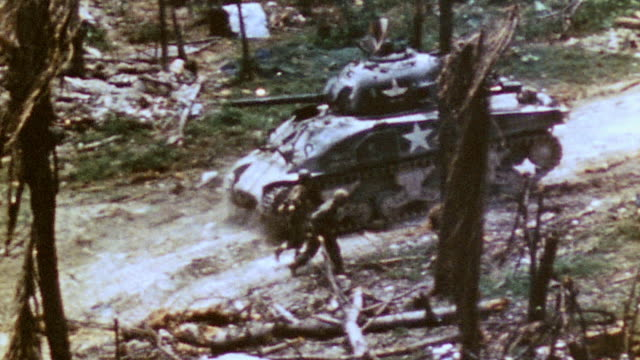 ha infantry and m4 sherman tanks advancing together up wooded slope / iwo jima japan - schlacht um iwojima stock-videos und b-roll-filmmaterial