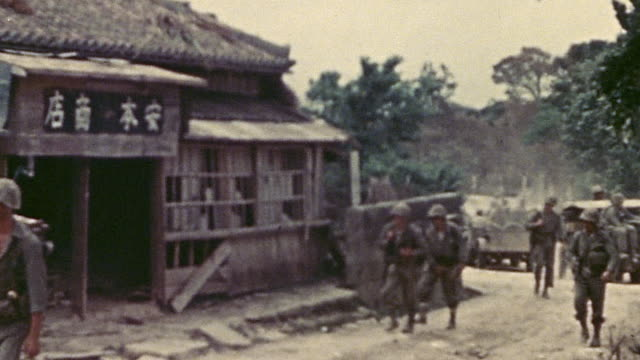 S infantry and vehicles leisurely advancing through village during WWII / Okinawa Japan