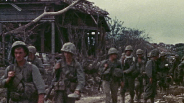 S infantry carrying weapons and supplies advancing through bomb damaged village during WWII / Okinawa Japan