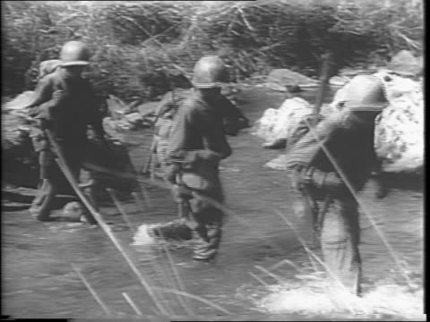 infantry crossing stream in luzon / montage of soldiers in line climbing hill, throwing grenades / montage of grenades exploding, soldiers moving... - filippine video stock e b–roll