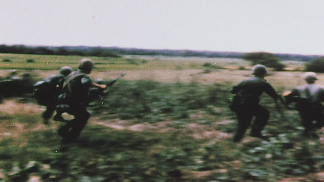 Infantry running into battle across field and officer on radio calling in fire support / Bau Bang Vietnam