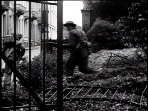 infantry soldiers running downhill / soldiers crossing courtyard / street with burning building / tank driving past crouching soldier - soldat stock-videos und b-roll-filmmaterial