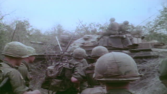 vídeos de stock, filmes e b-roll de ha infantry watching m48 patton tank driving by before continuing on foot / vietnam - formato letterbox