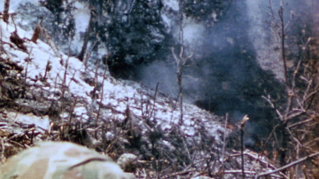 infantrymen crouched on scorched hillside flamethrower spewing flames uphill and brush burning / iwo jima japan - schlacht um iwojima stock-videos und b-roll-filmmaterial