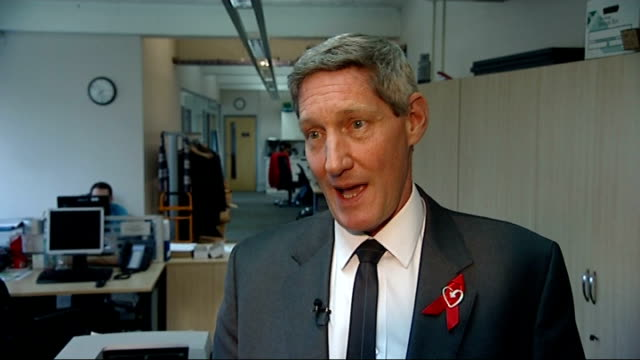 calls for at-risk groups to be regularly screened; sir nick partridge interview sot close shots of leaflets and posters with information about hiv - retrovirus video stock e b–roll