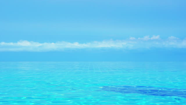 infinity edge pool surface and blue sky - infinity pool stock videos & royalty-free footage