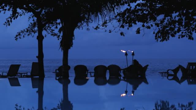 vídeos de stock, filmes e b-roll de infinity pool at a tropical resort - tocha tiki