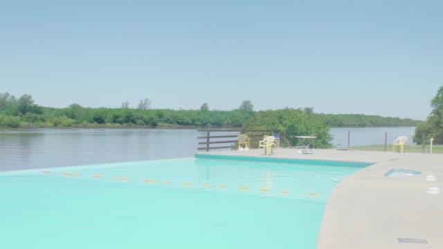vídeos de stock, filmes e b-roll de infinity pool at resort overlooking river - lago infinito