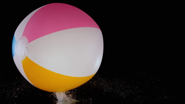 slo mo ld inflatable beach ball bouncing on black surface - rimbalzare video stock e b–roll