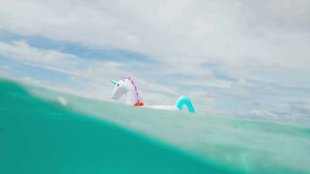 vídeos de stock e filmes b-roll de inflatable unicorn float in tropical maldives water - boia equipamento de desporto aquático