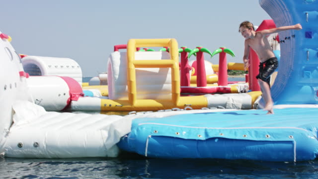 Inflatable water fun park in Kavos / Corfu / Greece, starring a 10 years old boy with blonde hair wearing black swimming shorts.