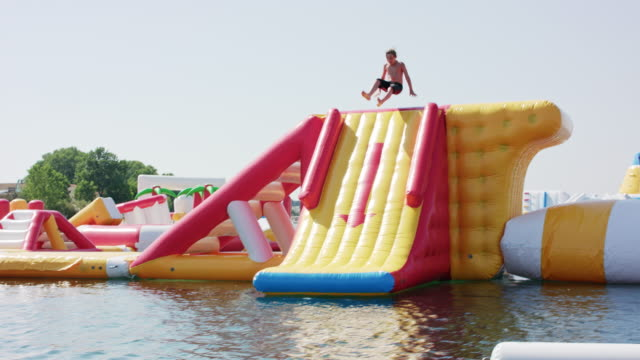 vídeos de stock, filmes e b-roll de inflatable water fun park in kavos / corfu / greece, starring a 10 years old boy with blonde hair wearing black swimming shorts. - enchendo