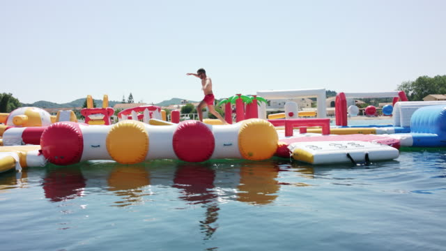 Inflatable water fun park in Kavos / Corfu / Greece, starring a sporty and sexy tanned male model with short dark hair wearing red swimming shorts.