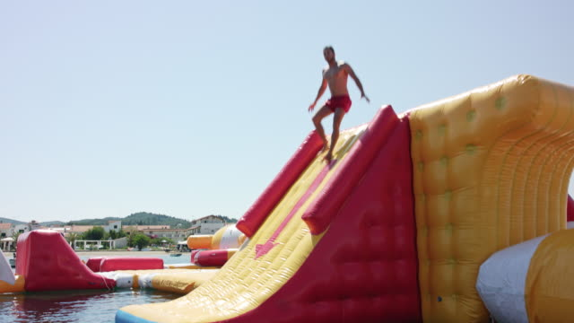 inflatable water fun park in kavos / corfu / greece, starring a sporty and sexy tanned male model with short dark hair wearing red swimming shorts. - water slide stock videos & royalty-free footage
