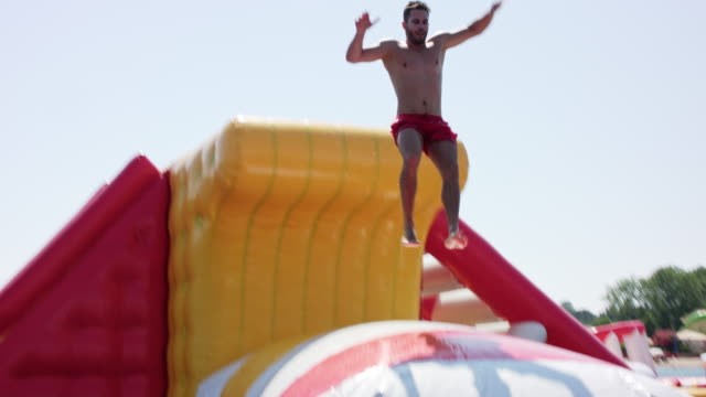 inflatable water fun park with flip in kavos / corfu / greece, starring a sporty and sexy tanned male model with short dark hair wearing red swimming shorts. - pillow stock videos and b-roll footage