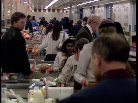 vídeos de stock e filmes b-roll de inflation down inflation down sainsburys tms people at checkouts cms goods along checkout conveyor towards put into bag - sainsburys