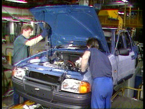 stockvideo's en b-roll-footage met inflation/ manufacturing output; ???: body of car lowered onto chassis tcms man fitting car body men working on car - chassis