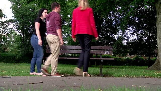 stockvideo's en b-roll-footage met ext various of anthony johnson his partner joanna ahmed pushing their children on swings at playground reporter along to bench with johnson and ahmed... - munt culinair