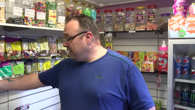 Hertfordshire Watford INT Sweets weighed on scales Customer paying for bag of sweets Bags of sweets and jars of sweets on display Paul Kiff interview...