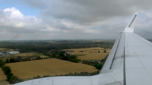 Inflight window wing view from landing airplane at London Stansted Airport STN EGSS in England UK with view over the countryside fields during the...