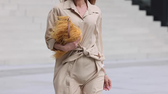 influencer gitta banko wearing a beige longsleeve silk maxi shirt dress with tied waist by p.a.r.o.s.h., a brown-orange feather bag by... - satin stock videos & royalty-free footage