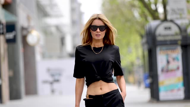 influencer gitta banko wearing a black t-shirt by zara, black pants with hip cut out and the gold logo by versace, black mesh pumps by bottega... - ヴェルサーチ点の映像素材/bロール