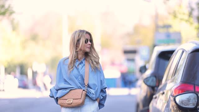 influencer gitta banko wearing a blue oversize blouse by sosue, light blue denim jeans pants by lala berlin, a beige baguette bag by fendi, black and... - zebra print stock videos & royalty-free footage