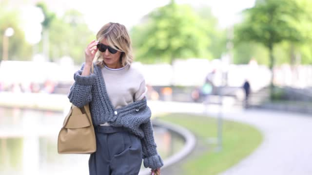 influencer gitta banko wearing a grey knitted cardigan by isis von arnim, a beige t-shirt by brunello cucinelli, grey pants by brunello cucinelli,... - cardigan sweater stock videos & royalty-free footage