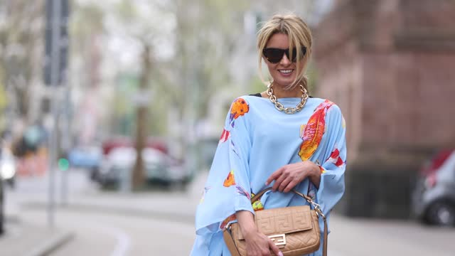 influencer gitta banko wearing a light blue maxi dress with multicolor koi fish print by simone bruns, a beige baguette bag by fendi, yellow sandals... - arts culture and entertainment stock videos & royalty-free footage