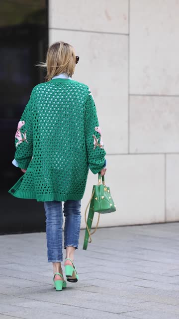 vidéos et rushes de influencer gitta banko wearing a side braid hairstyle, a green oversize crochet cardigan with floral embroidery by valentino, a light blue oversize... - cardigan