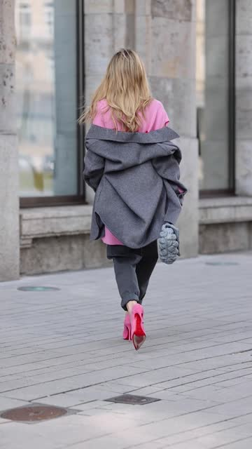 vidéos et rushes de influencer gitta banko wearing an oversize grey jacket by akne studios, a pink cardigan with cut out details by givenchy, dark grey denim jeans pants... - cardigan