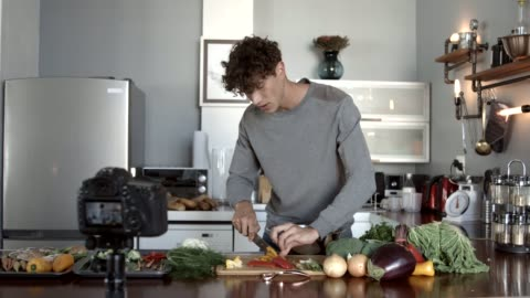 vídeos y material grabado en eventos de stock de influencer making video while cutting bell pepper in kitchen - hombres jóvenes