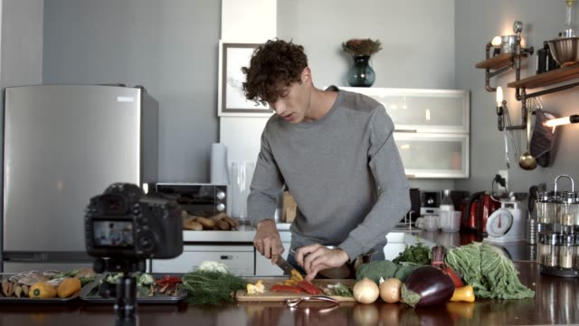 influencer making video while cutting bell pepper in kitchen - garkochen stock-videos und b-roll-filmmaterial