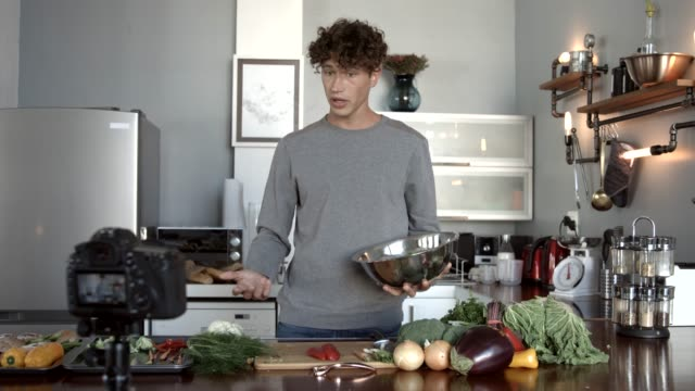 vídeos de stock e filmes b-roll de influencer making video while preparing vegetables in kitchen - trabalho de freelancer